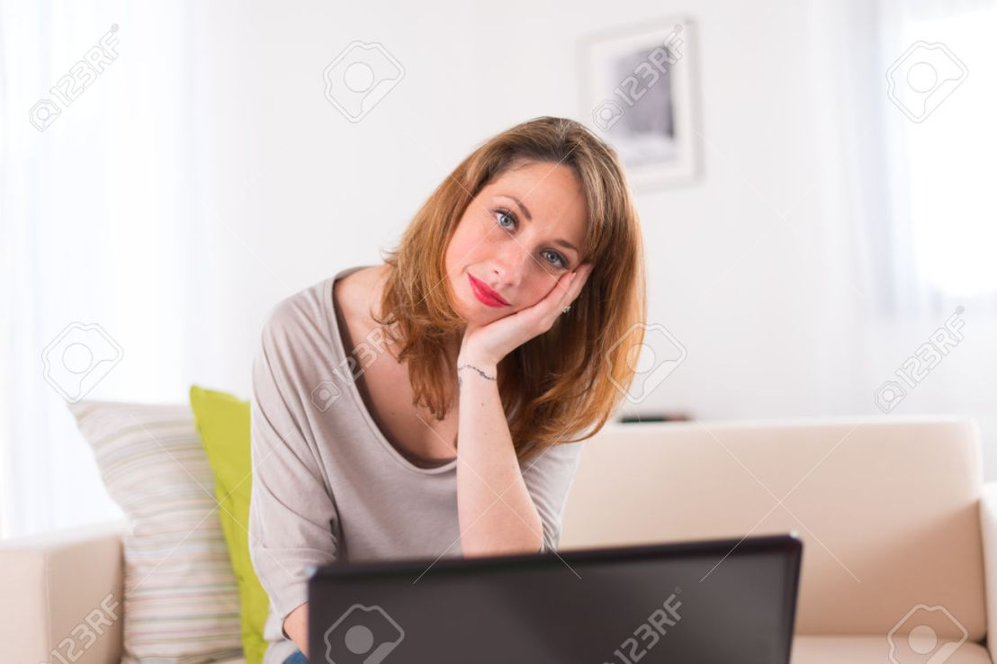 cheerful young women at home working on her laptop computer